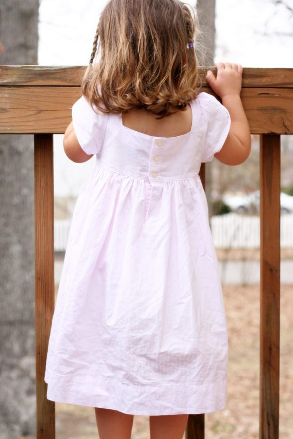 Zoe wearing a striped pink dress, facing away.