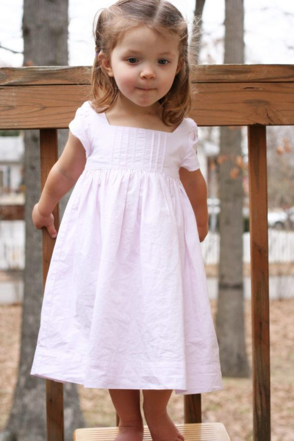 Zoe in a pink dress, facing the camera.