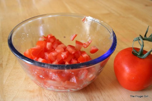 A glass bowl full of chopped tomatoes.