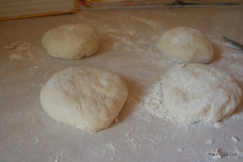 Three balls of pizza dough on a counter.