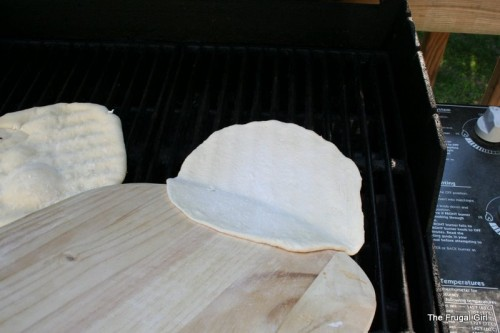 Dough sliding onto a grill from a pizza peel.