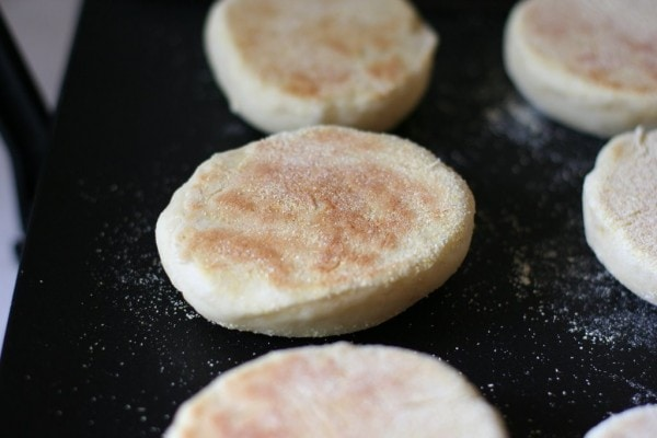 Partially-cooked English muffins on a griddle.