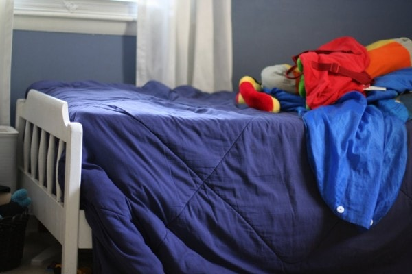 A white twin bed with a blue comforter.