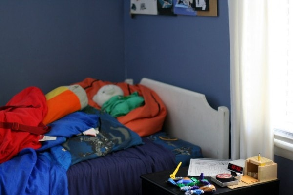 A white twin bed in a room with blue walls.