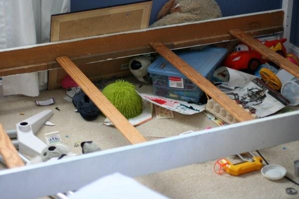 Clutter under a bed frame.
