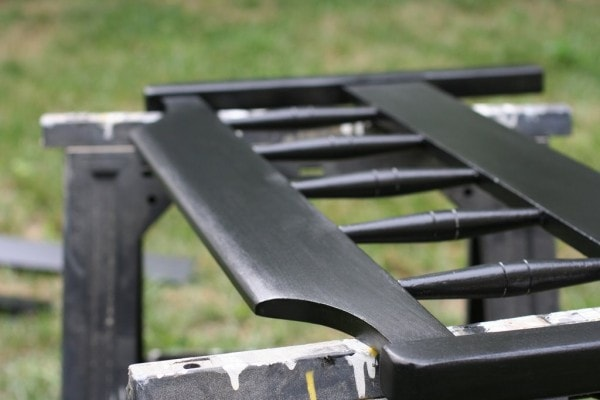 A black painted footboard on saw horses.
