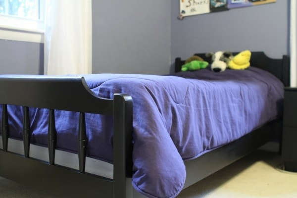 Black twin bed with blue comforter.