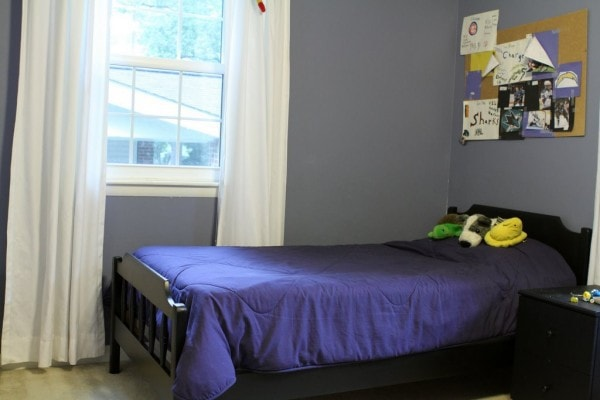 Black twin bed in a room with blue walls.