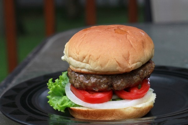 A burger in a bun with lettuce, tomato, and onion.