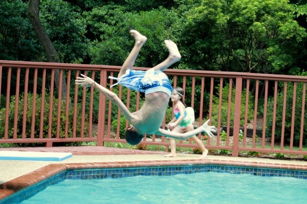 A kid doing a flip into a pool.