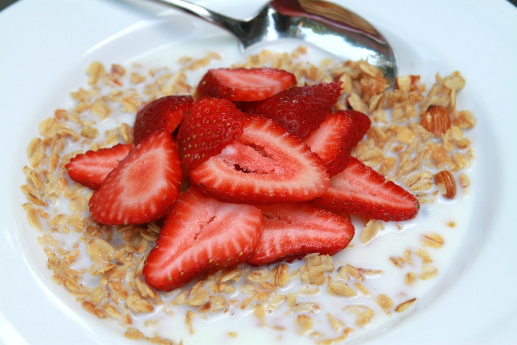 A bowl of granola, topped with strawberries and milk.
