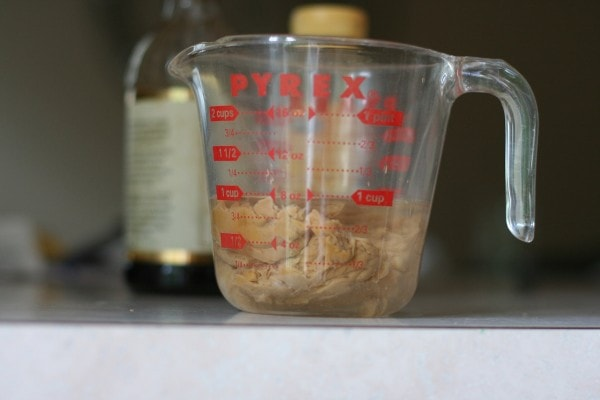 Peanut butter and water in a glass Pyrex measuring cup.