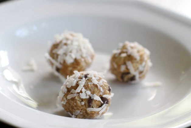 Chocolate chip peanut butter energy balls on a white plate.