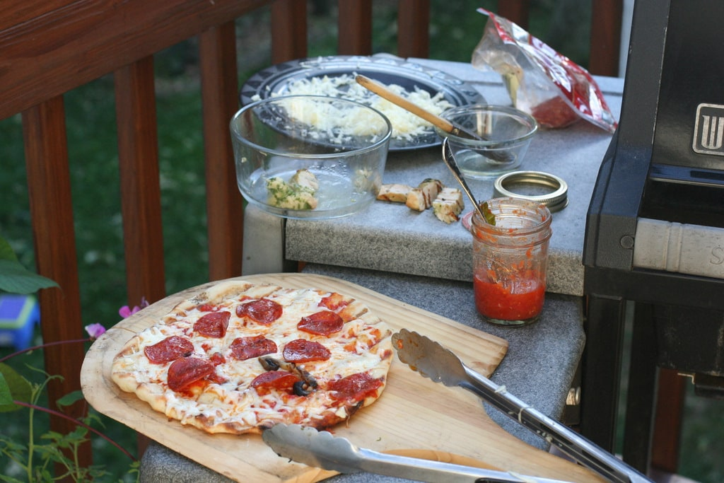 A view of a grill with pizza-making ingredients on the side shelf.