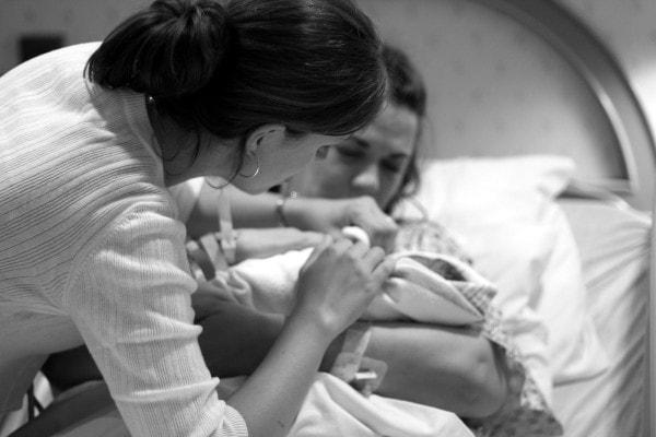Kristen helping a mom with a newborn.