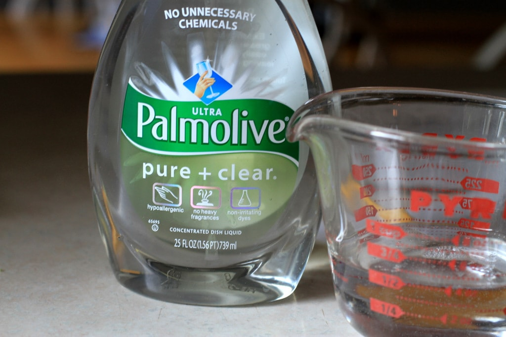 Dish soap next to a measuring cup.