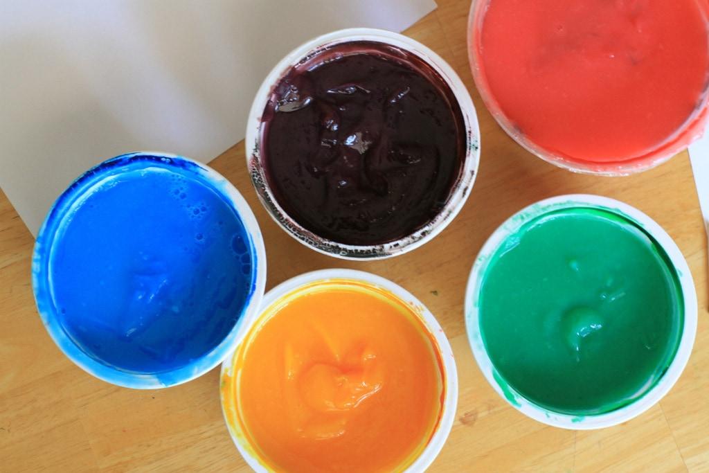 Colorful pots of finger paint.