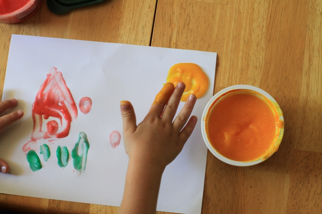 A child's hand using finger paint.