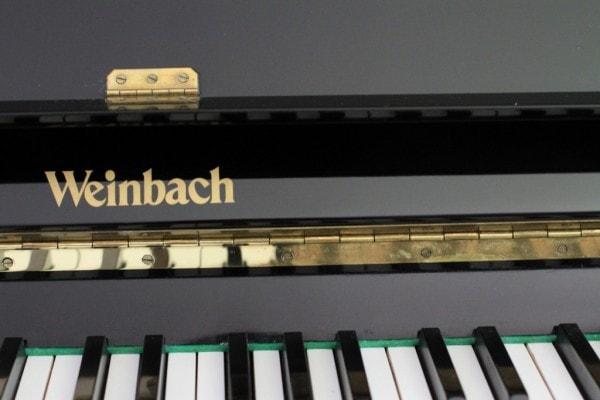 The keys on a black Weinbach piano.