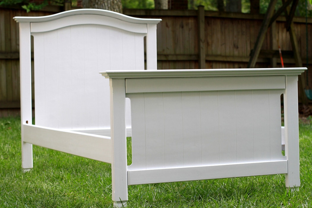 A white twin bed frame sitting on a green lawn.