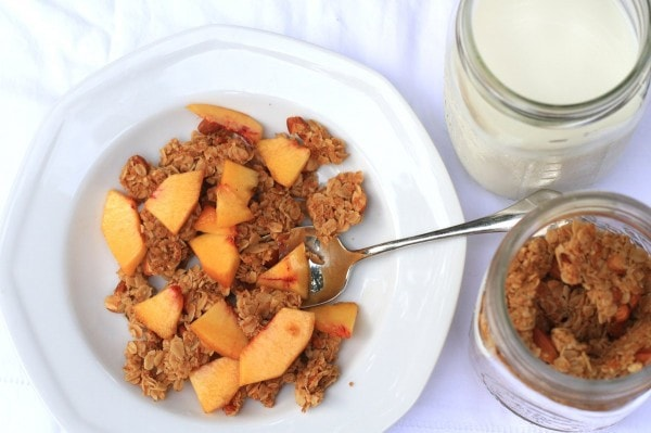 A bowl of granola, topped with sliced peaches, in a white bowl.