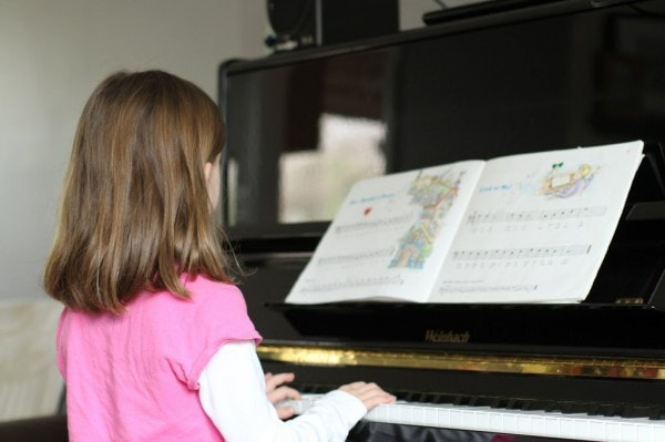 A little girl in a pink shirt practicing piano.