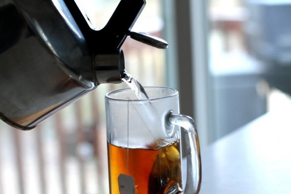Water pouring from a kettle into a glass mug with a tea bag in it.