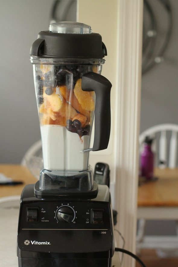 A vitamix blender filled with yogurt and fruit.