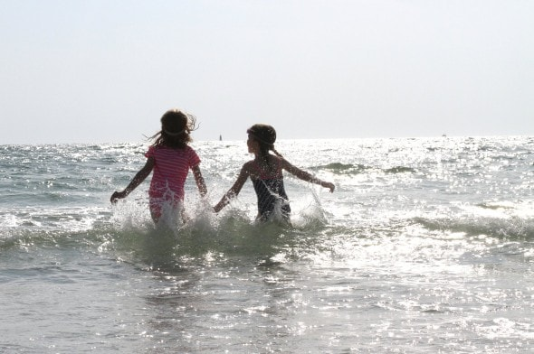 girls jumping in waves