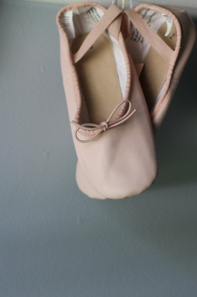 A pair of pink ballet shoes hanging from a hook.