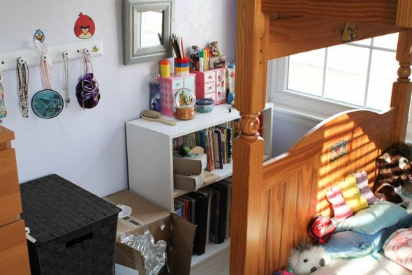 A tidied child's bedroom with a bunkbed in view.