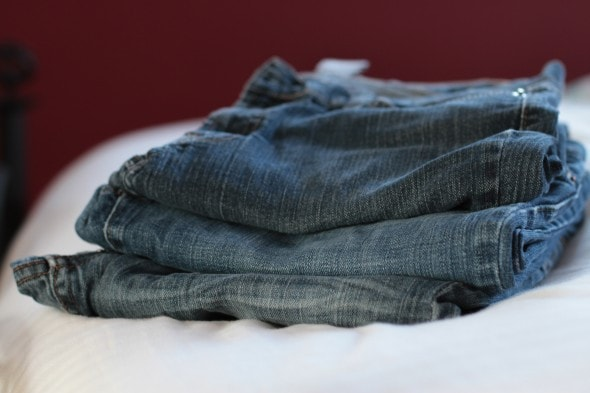 Three pairs of jeans, folded and stacked on a bed.