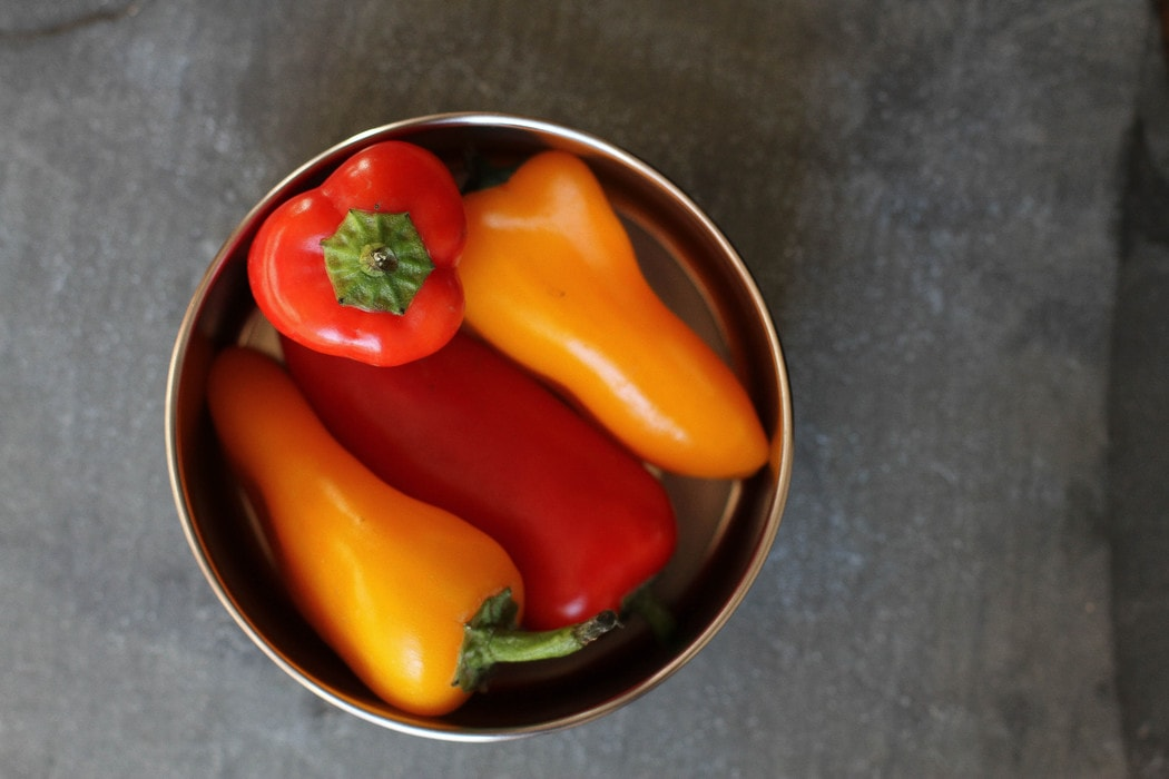 Mini peppers in a stainless steel container.