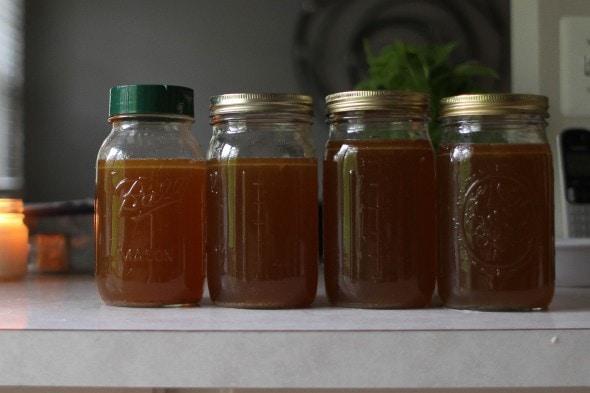 Four glass Mason jars of dark brown chicken broth.