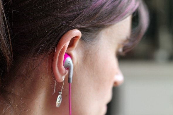 An ear with a pink earbud inserted.