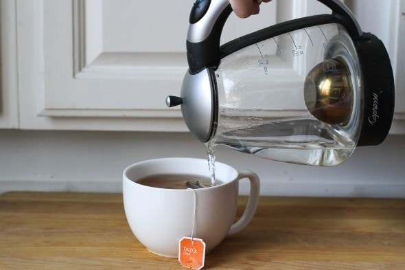 A Capresso electric kettle pouring into a tea cup.