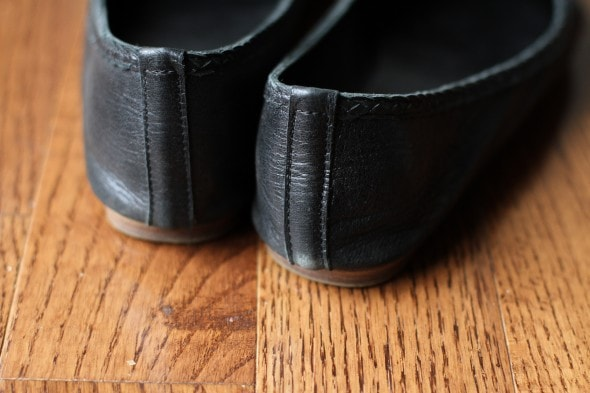 Two black ballet flats on a wood floor.