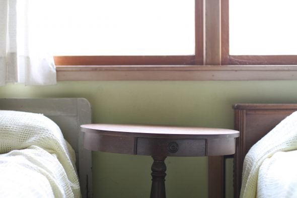 A round wooden night table against a green wall.