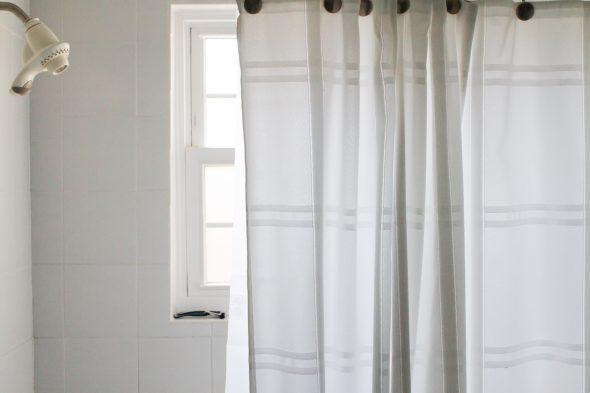 A white bathtub with a white shower curtain.