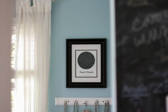 A black framed star map hung on a teal wall.