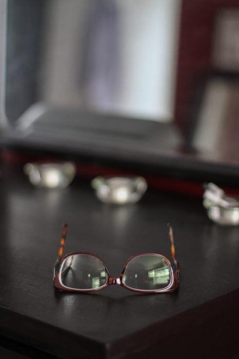 A pair of glasses on a black dresser top.