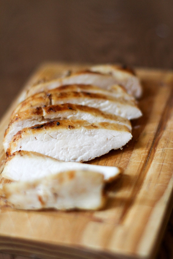 Brineraded, sliced chicken breast on a wooden cutting board.