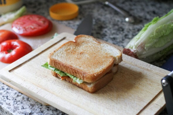 A grilled BLT sandwich on a wooden cutting board.