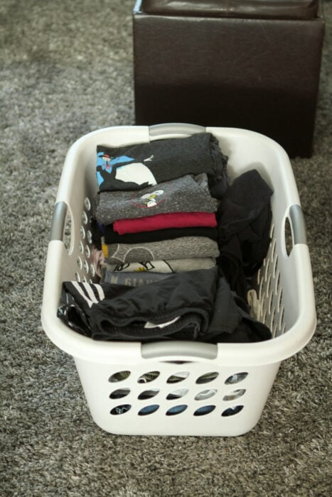 folded laundry in a white basket.
