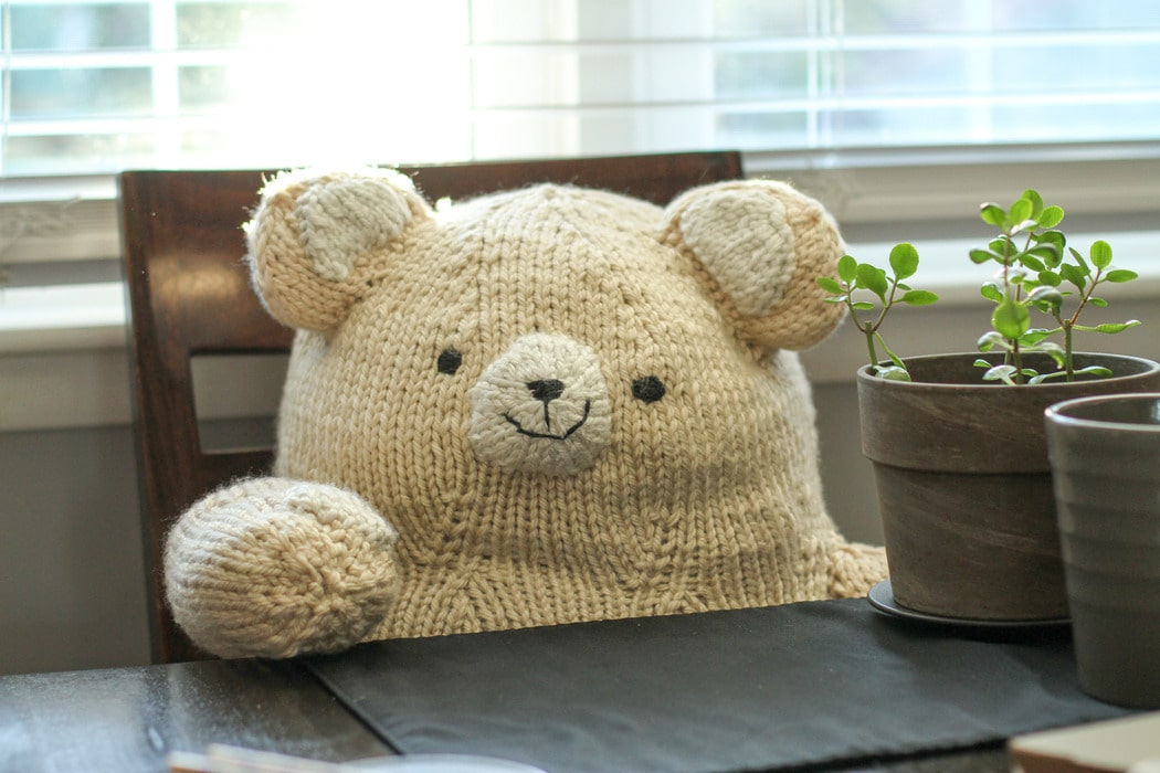 A large white knitted bear, sitting in a chair.