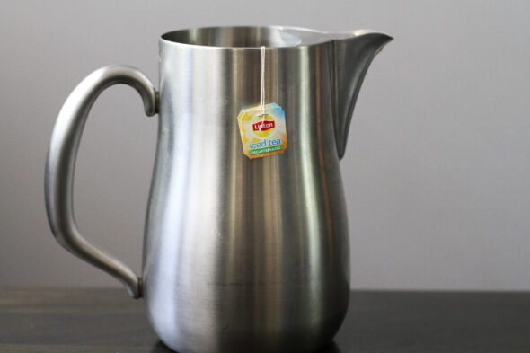 iced tea in a stainless steel pitcher