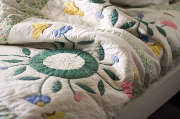 flowered quilt on white twin bed