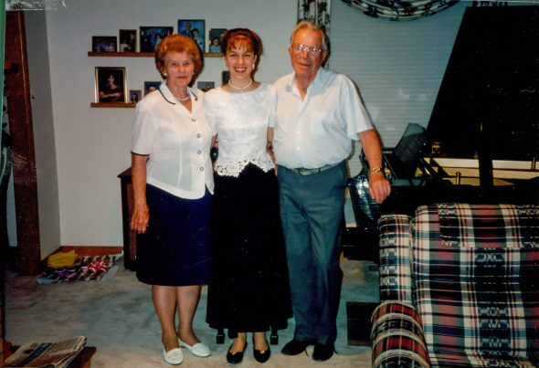 Kristen and her grandparents standing by a piano