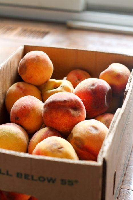 cardboard box of bruised peaches