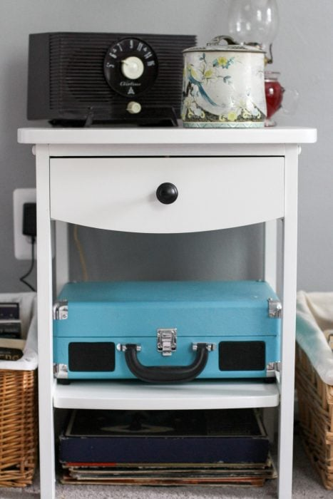 teal record player on white shelf